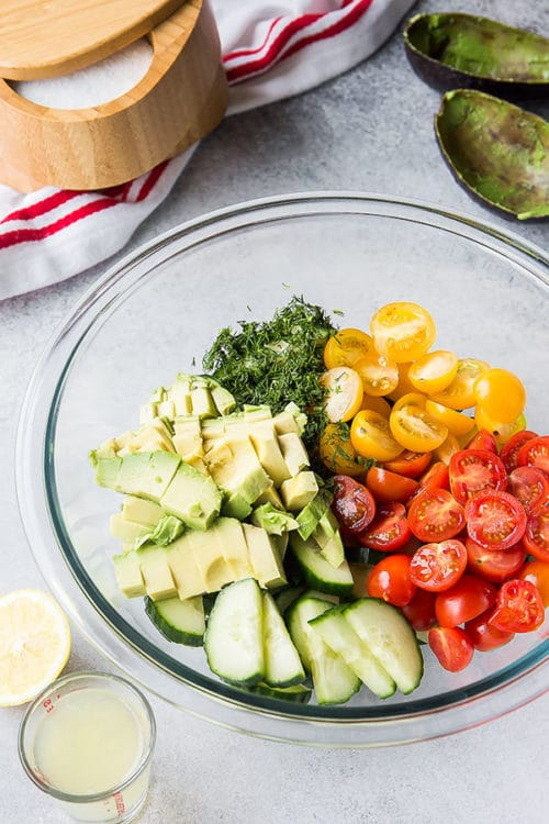 Our family loves this easy cucumber salad with creamy avocado lemon dressing. You're going to LOVE this light and healthy summer salad for your grilled steak or chicken on a busy weeknight! #cucumbertomatosalad #salad #cucumbersalad #sidedish #busycooks