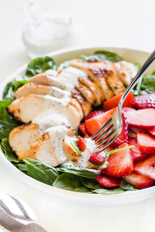 Satisfying strawberry spinach salad with grilled chicken and creamy poppy seed dressing is a perfect weeknight dinner on a hot summer day. The dressing can be prepared in advance, grilling the chicken takes less than 30 minutes, which means you can toss this salad together in less than 45 minutes! #chickensalad #strawberryspinachsalad #salad #summersalad #weeknightmeal #easydinner #poppyseeddressing #busycooks
