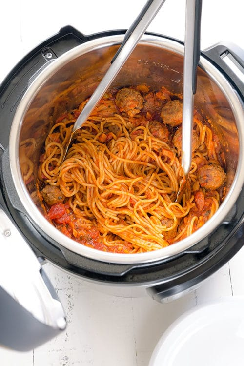 Instant Pot Spaghetti and Meatballs - instant comfort meal with only 3 main ingredients under 30 minutes! Your favorite jar of pasta sauce and frozen meatballs are our secret shortcut to this quick and easy one pot spaghetti meal. It's going to be your family favorite in no time. #spaghettiandmeatballs #meatballs #pasta #quickdinner #easydinner #instantpot #instantpotpasta #busycooks