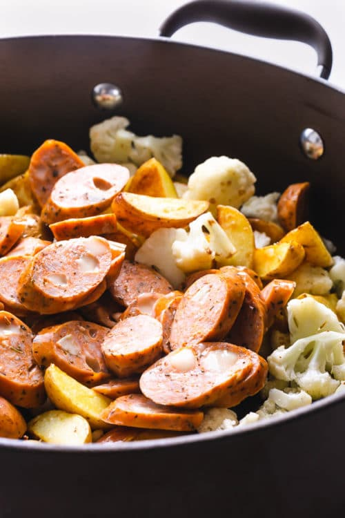 Sliced sausage tossed into a skillet with baby potatoes and cauliflower to make a 20-minute sausage and potatoes skillet.