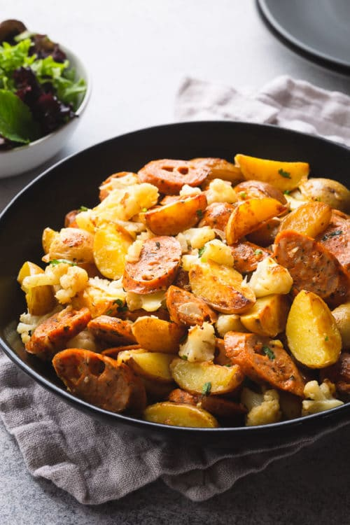 A large serving bowl of sausage and potatoes skillet, a small bowl of green salad and stack of dinner plates.