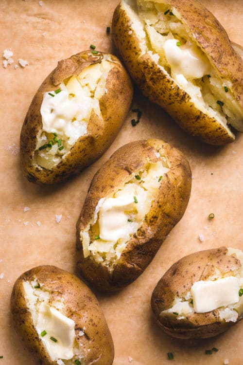 "Perfectly ""baked"" potatoes loaded with butter and chives cooked in an Instant Pot and finished in the oven for crispy skin!"
