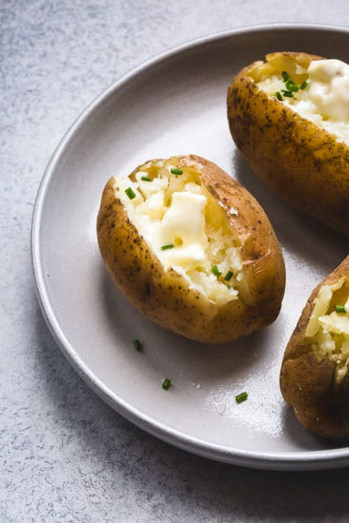 Butter loaded Instant Pot baked potatoes on a serving platter.