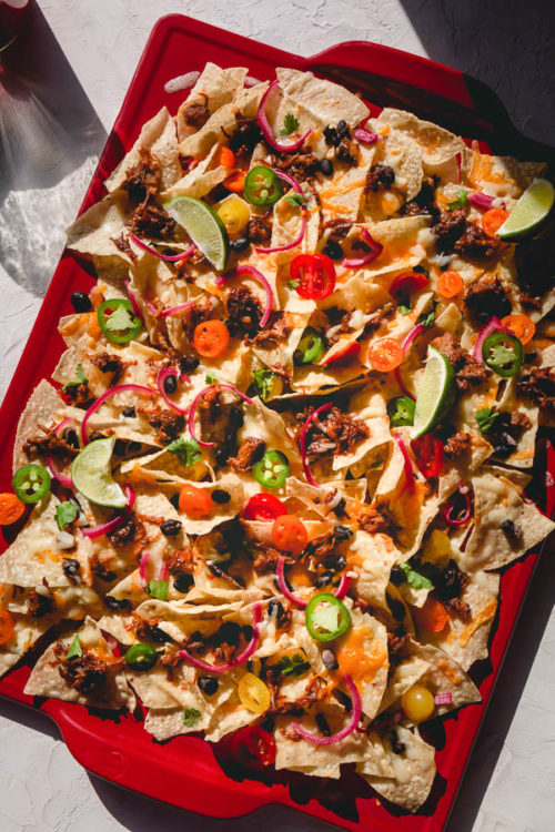 Here's the best nachos recipe around!  Making the best nachos is less about how much ingredients to use, and is more about layering the ingredients properly for the best possible result. #nachos #bestnachos #pulledporknachos