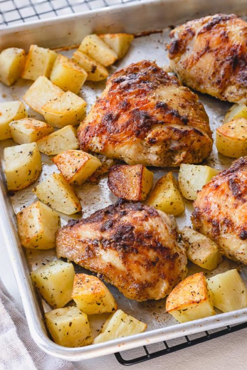 These baked mustard chicken thighs and potatoes are a flavorful and satisfying comfort meal, quick enough to make on a busy weeknight! #chickenthighs #roastchikenthighs