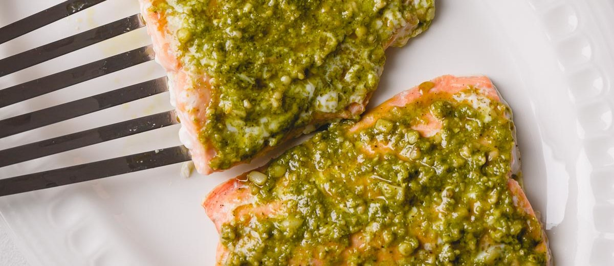 Tender soft baked salmon filet infused with herby pesto - perfect 30-minute dinner. #salmonrecipe