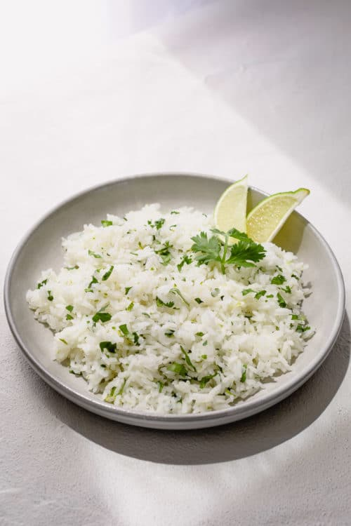 Try this flavorful Cilantro Lime Rice for a change. It's just as quick and easy as the plain rice, and super versatile! This zesty rice complements any Mexican and Asian dishes and pairs perfectly with any chicken, beef and pork! #cilantrolimerice