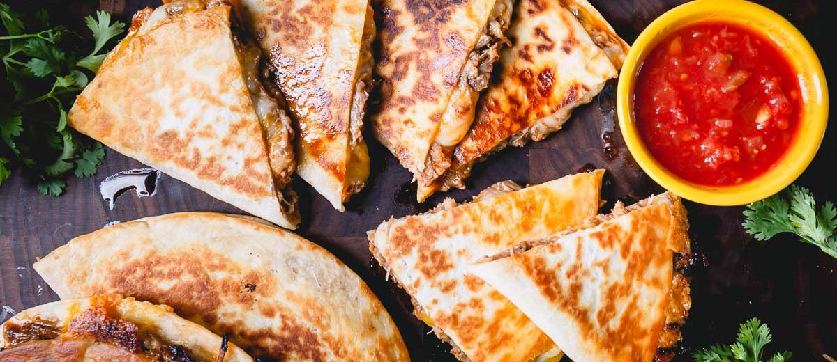 Seriously easy and delicious, these pulled pork quesadillas are my favorite way to use up leftover pulled pork! A perfect cook once, eat twice meal! #quesadillas #pulledporkquesadillas