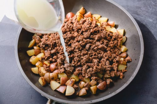 Step 3 for delicious ground beef potato hash: add a little liquid to cook the potatoes through.