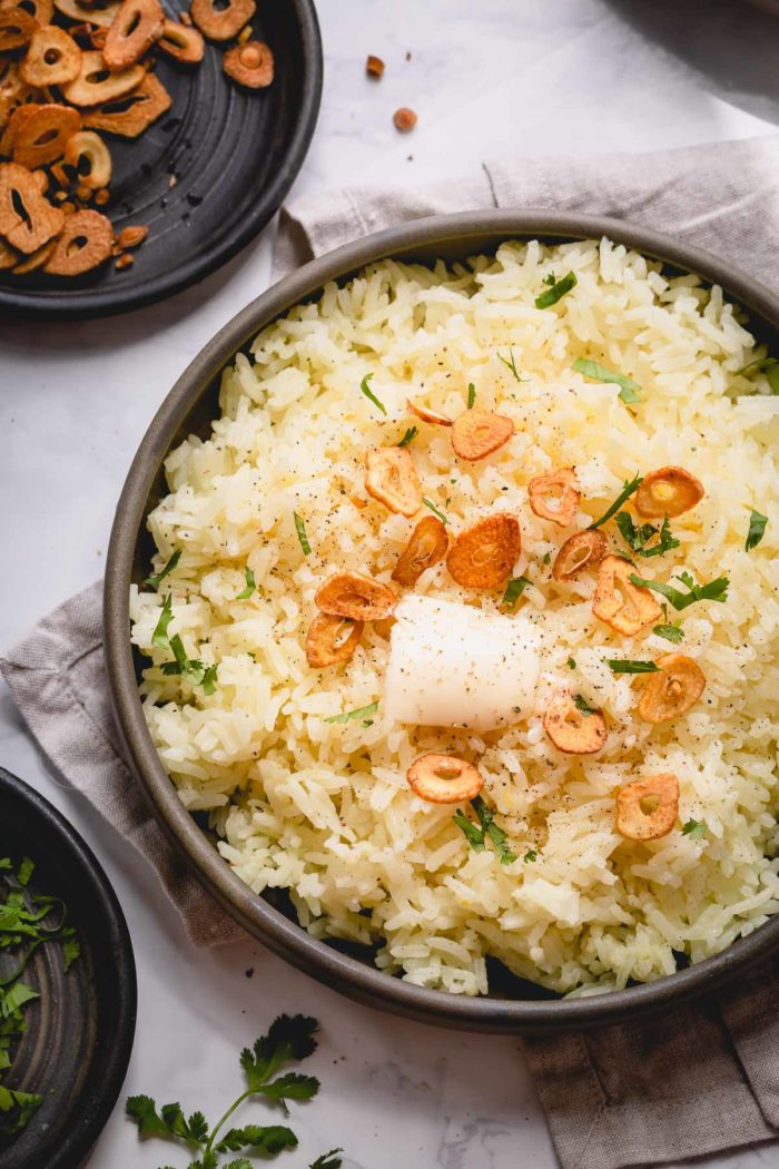 A shallow bowl of garlic butter rice topped with garlic chips, slice of butter and fresh herbs.